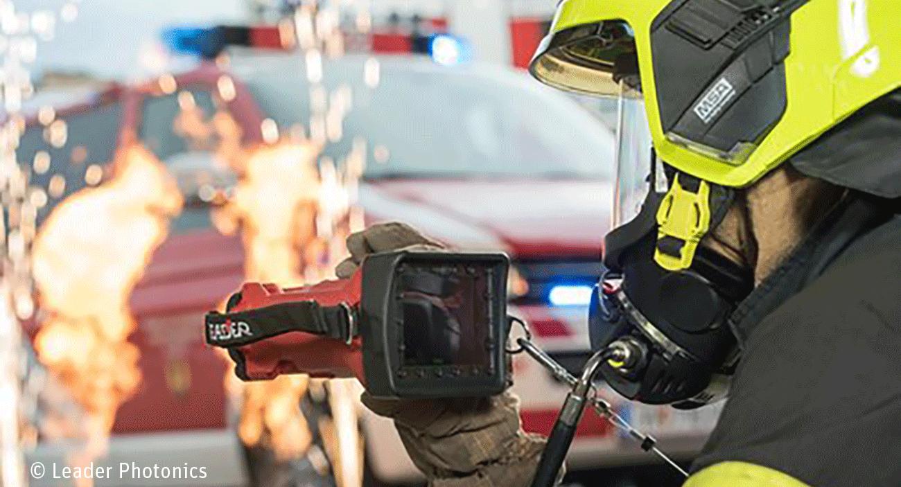 Ein Feuerwerhmann benutzt eine Wärmebildkamera. Im Hintergrund ist ein Feuerwehrauto zu sehen und es sprühen Funken